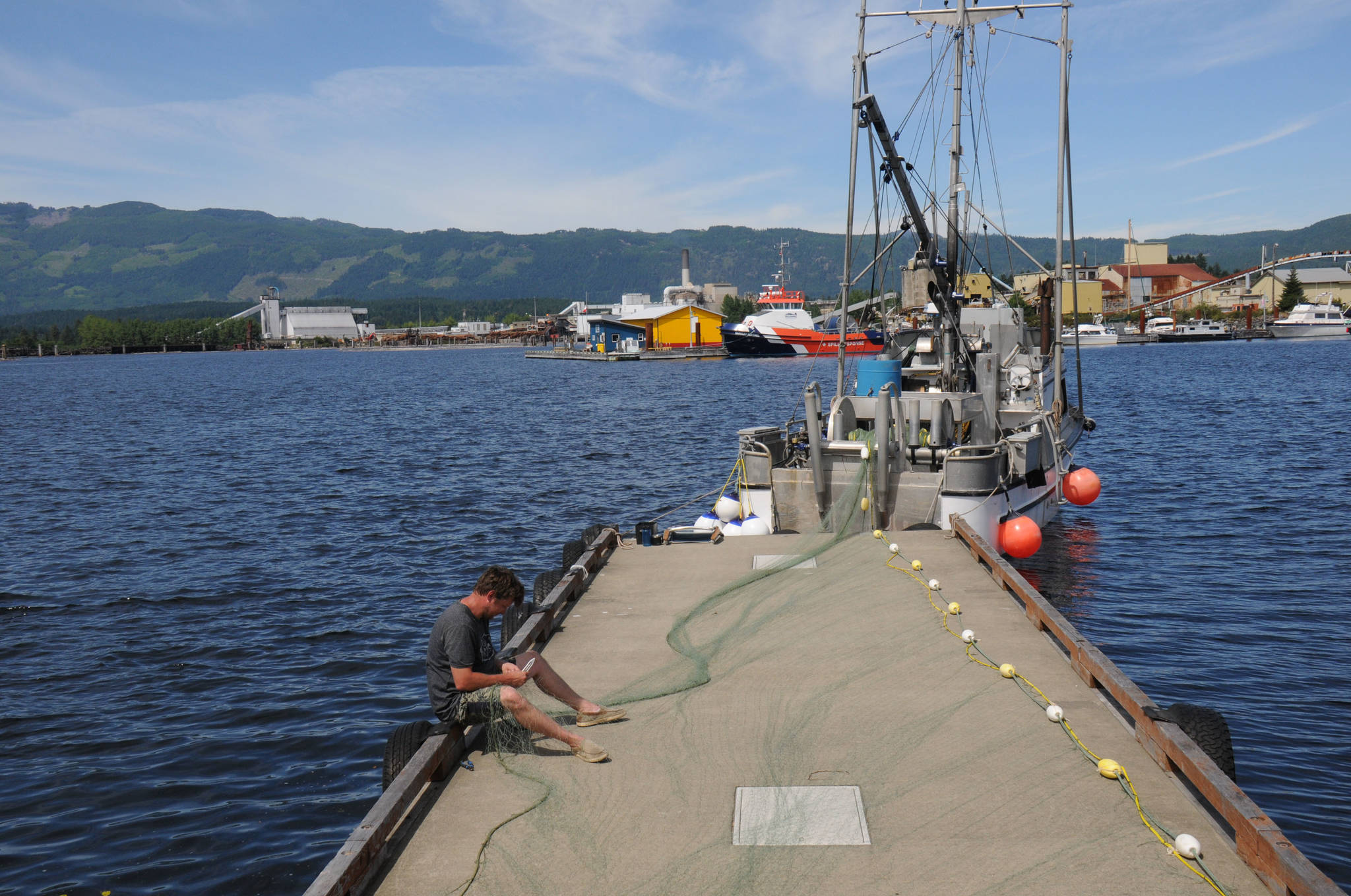 Commercial gillnet fisher Ryan Daynes repairs his net from the Lily M. on one of the wharf fingers at Centennial Pier, Port Alberni, on June 24, 2021. (SUSAN QUINN/ Alberni Valley News)