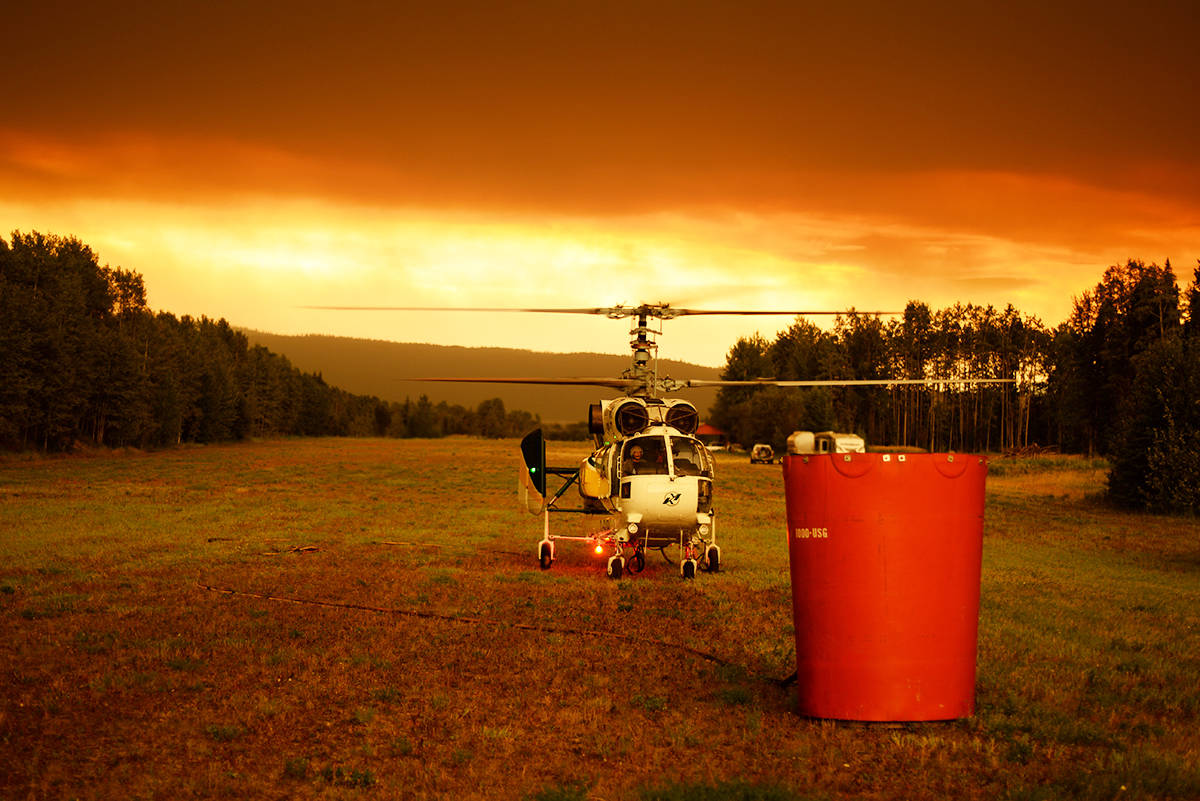 One of VIH Helicopters Kamov KA32 choppers fights fires using the bucket in the foreground. (Mario Vaillancourt photo/ VIH Helicopters)