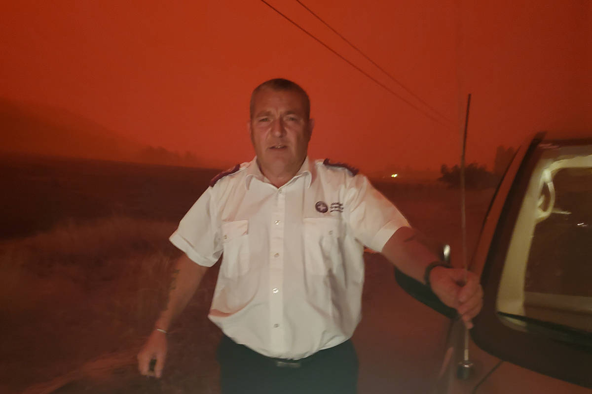 Trevor White, operations manager for the Abbotsford-based company Hospital Transfers, stands outside in the Okanagan while the sky turned red in the middle of the day due to wildfires, on Aug. 16, 2021. (Submitted)
