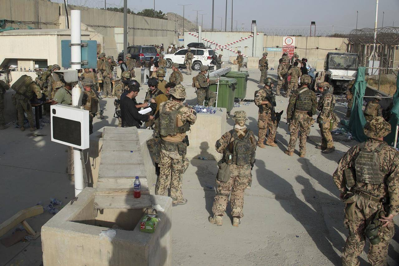 In this photo provided by the Ministry of Defence, members of the British and US military engage in the evacuation of people out of Kabul, Afghanistan on Friday, Aug. 20, 2021. (Ministry of Defence via AP)