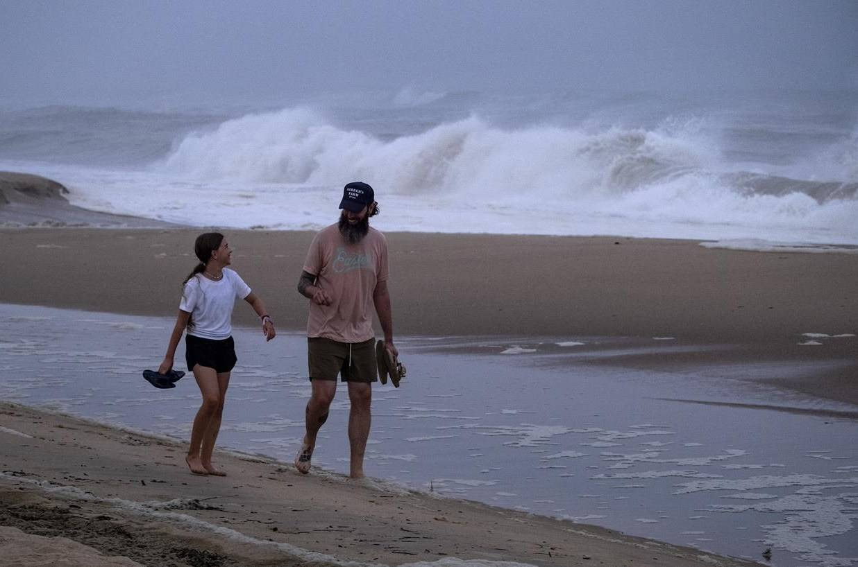 Ryan Madigan, and his daughter Charolette Madigan, 11, of Cold Spring Harbor, N.Y., stand along a beach in Montauk, N.Y., Saturday, Aug. 21, 2021, as Hurricane Henri churns up waves as the storm approaches. (AP Photo/Craig Ruttle)