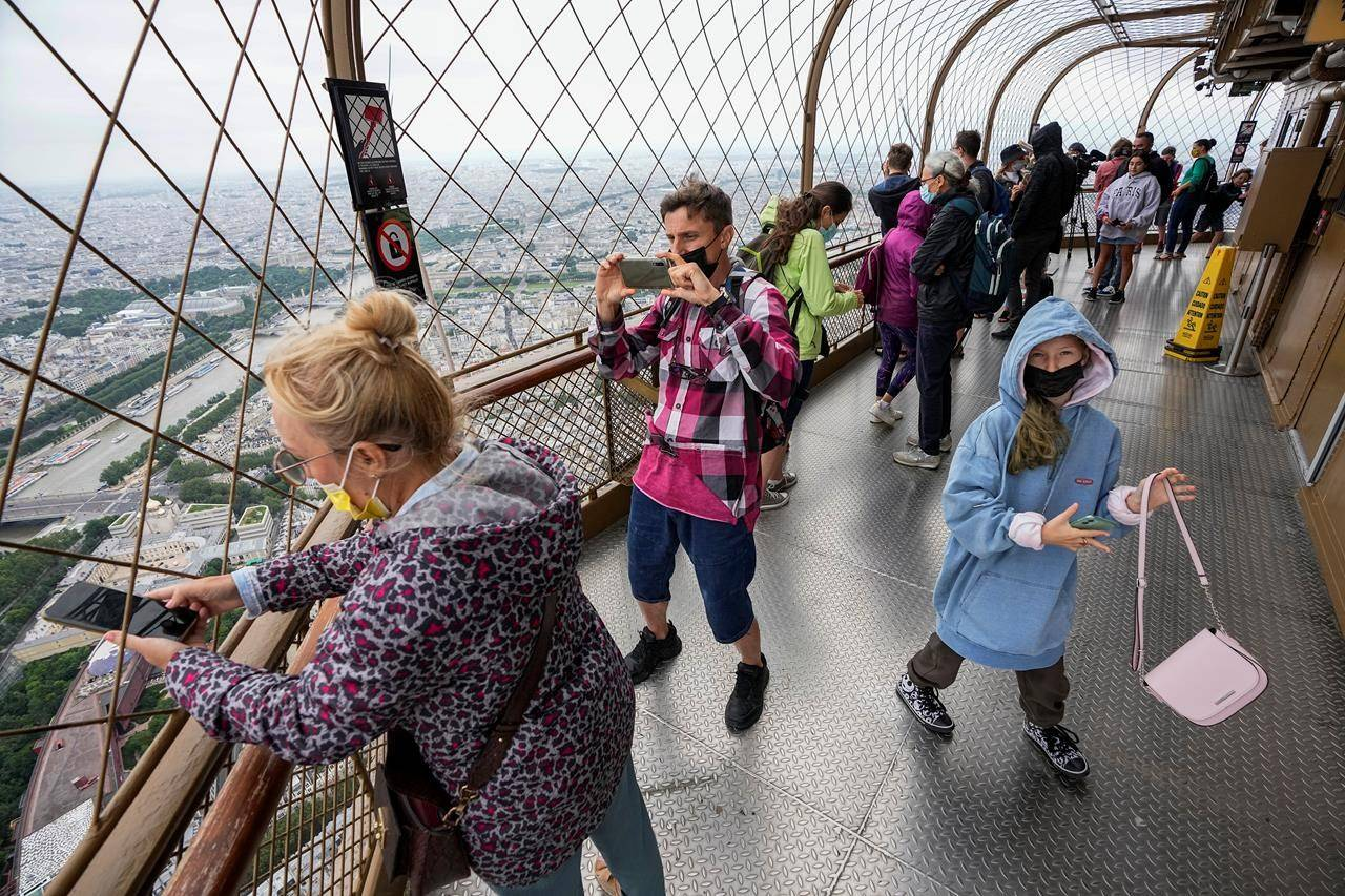 FILE - In this Friday, July 16, 2021 file photo, visitors enjoy the view from top of the Eiffel Tower in Paris. The European Union is expected to recommend that its member states reinstate restrictions on tourists from the U.S. because of rising coronavirus infection levels in the country, EU diplomats said Monday, Aug. 30. (AP Photo/Michel Euler, File)