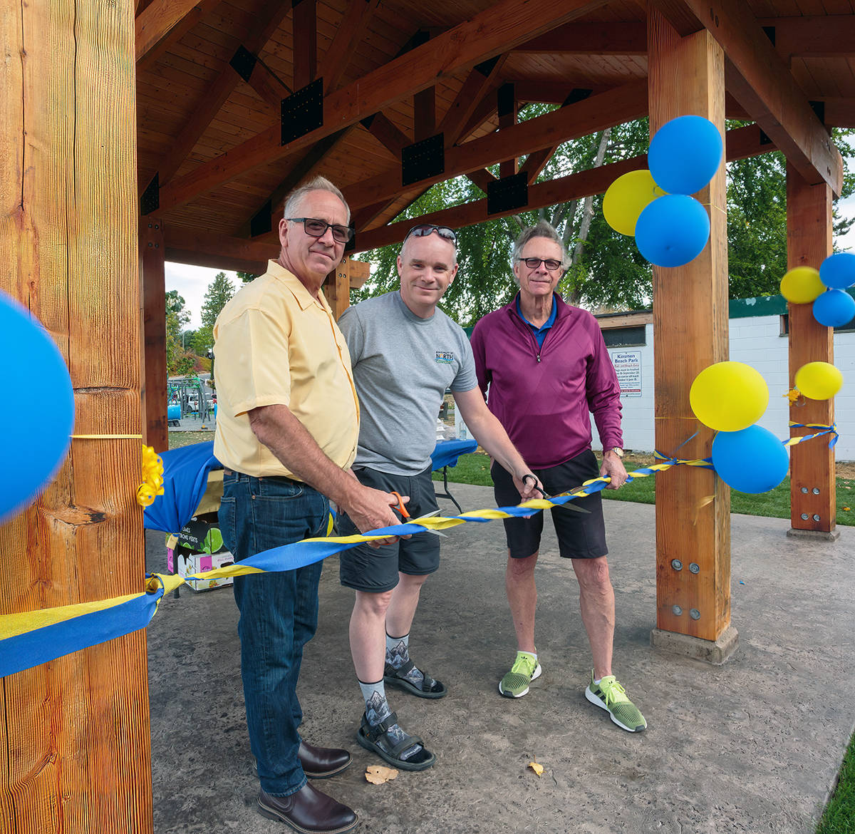 Ribbon-cutting by Ken Stanton and Don Stewart with Tom Andrews marks the official opening of the Rotary picnic shelter. (Photo by Art Carlyle)