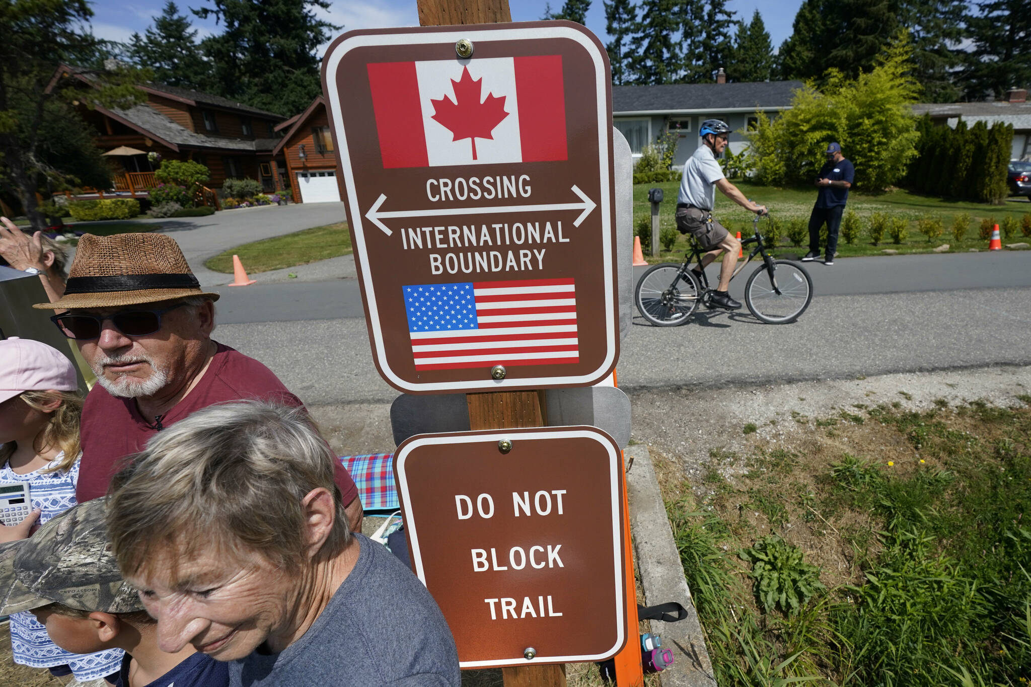 A family visits across the U.S.-Canada border at the Peace Arch Historical State Park as a cyclist rides past on the Canadian side, Monday, Aug. 9, 2021, in Blaine, Wash. A month after easing border restrictions for American citizens, Canada is following suit for other international travellers. (AP Photo/Elaine Thompson)