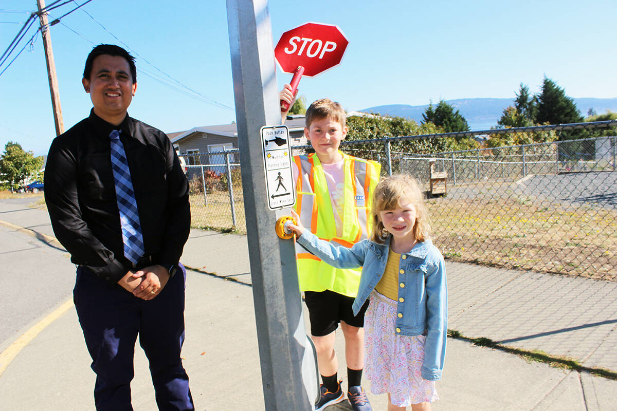 Charlotte Dyke, a Grade 1 student, presses the button at the crosswalk outside Crofton Elementary School on the first day back in school. Gavin Murray is there to be the crossing guard while principal Tim Ylagan makes sure safety is being practiced. (Photo by Don Bodger)