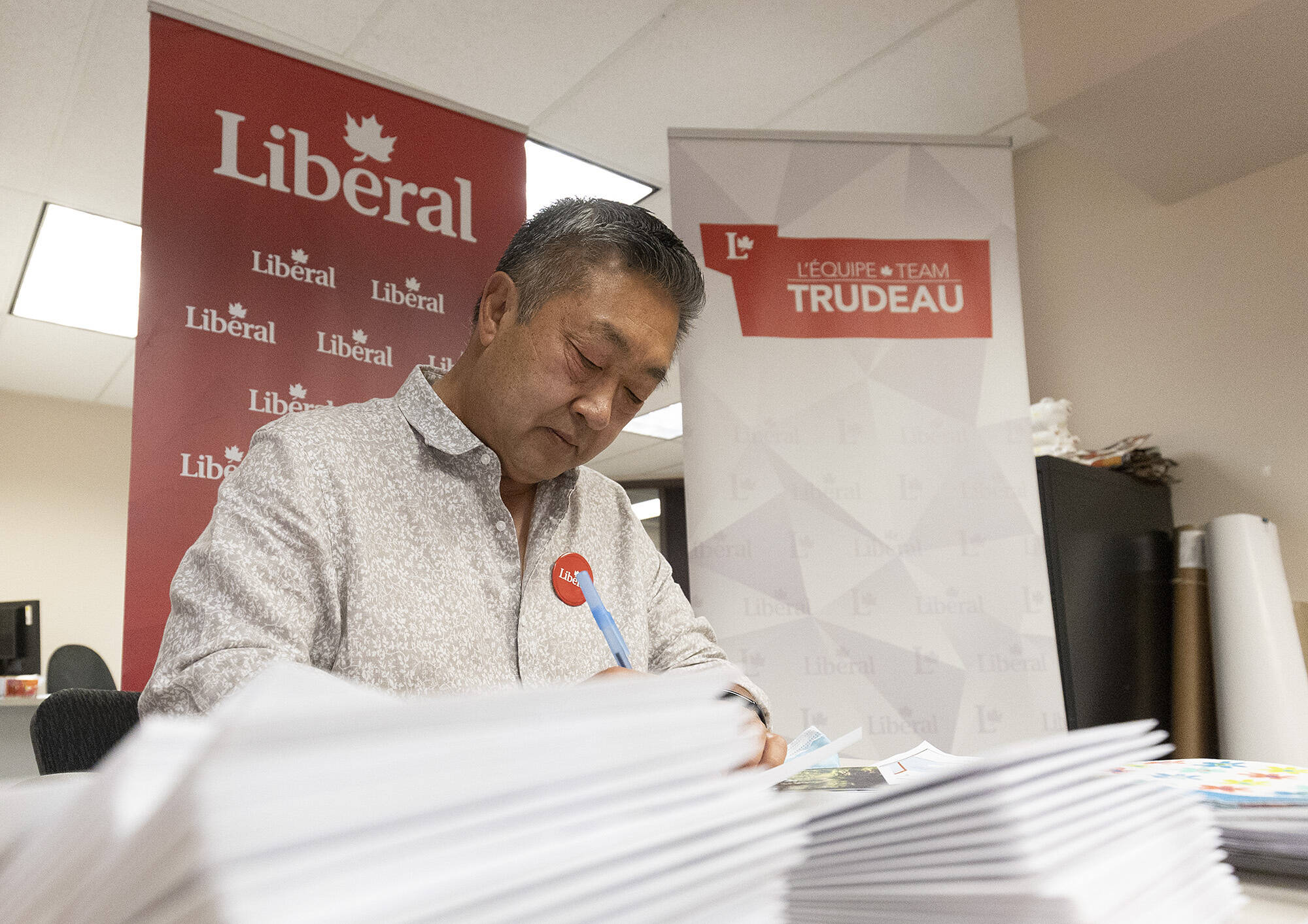 Federal Liberal candidate Doug Kobayashi signs thank you cards at his campaign office in Saanich on election day. (Arnold Lim/Black Press Media)