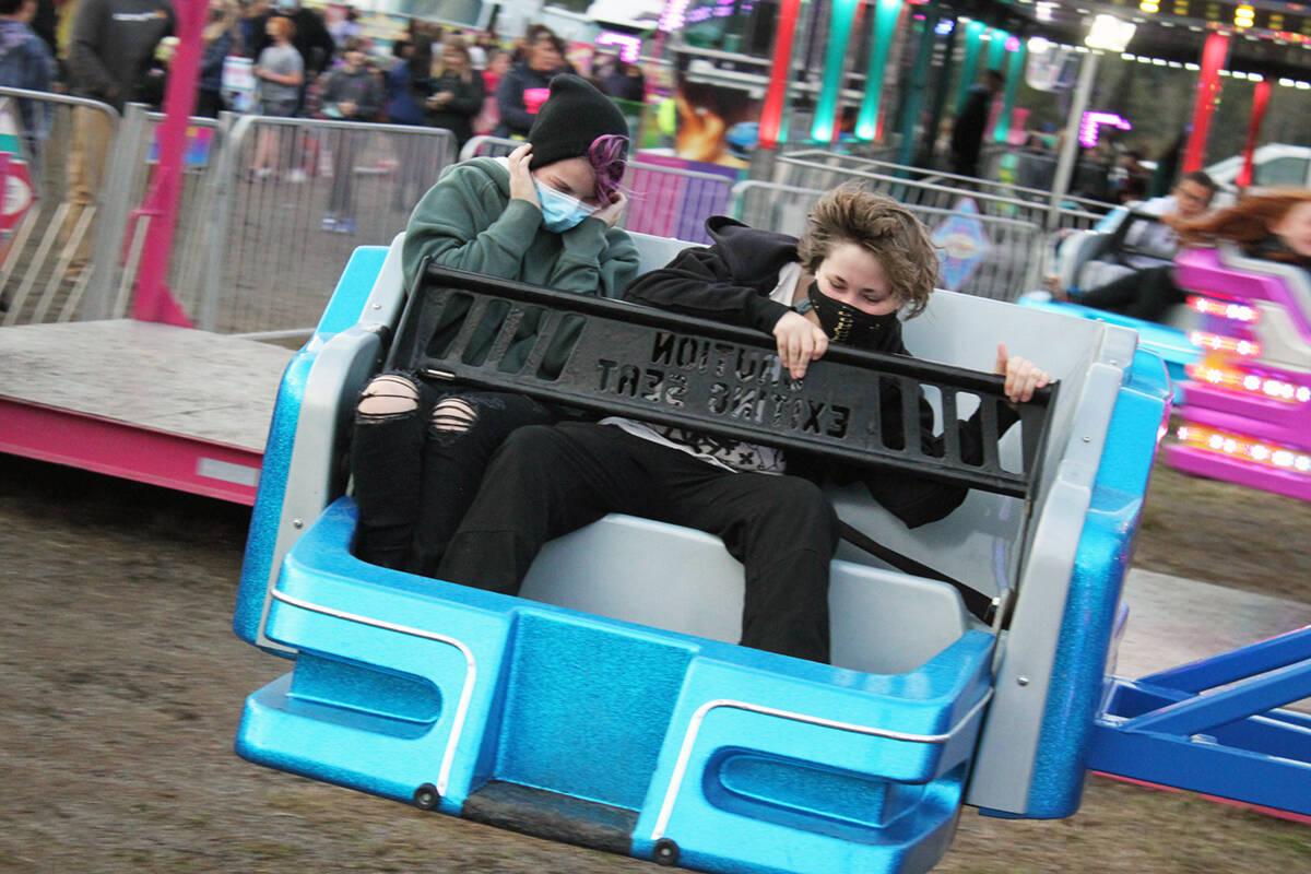 Abby Knight and Ciara Duggan mask up and have fun on a ride at the Cowichan Exhibition. (Photo by JoHannah Knight)
