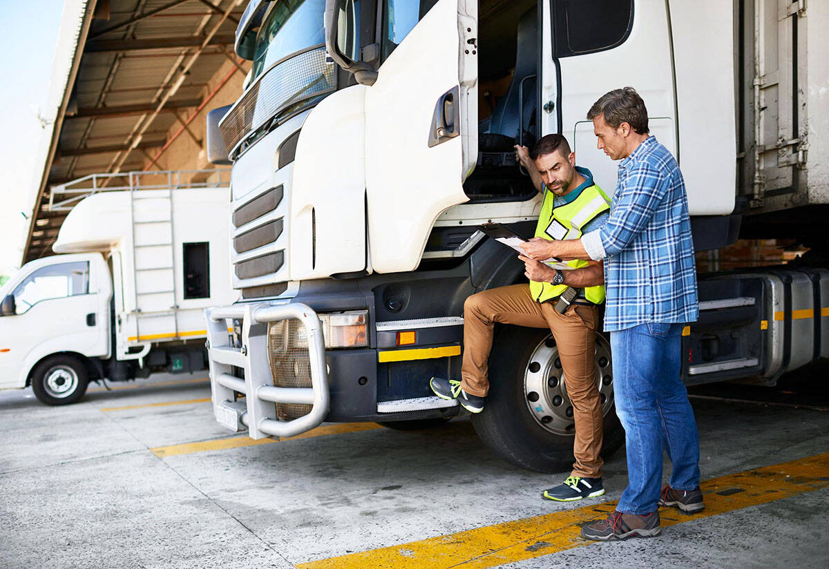 Two employees who drive for work review a safety checklist before getting behind the wheel. (iStock photo).