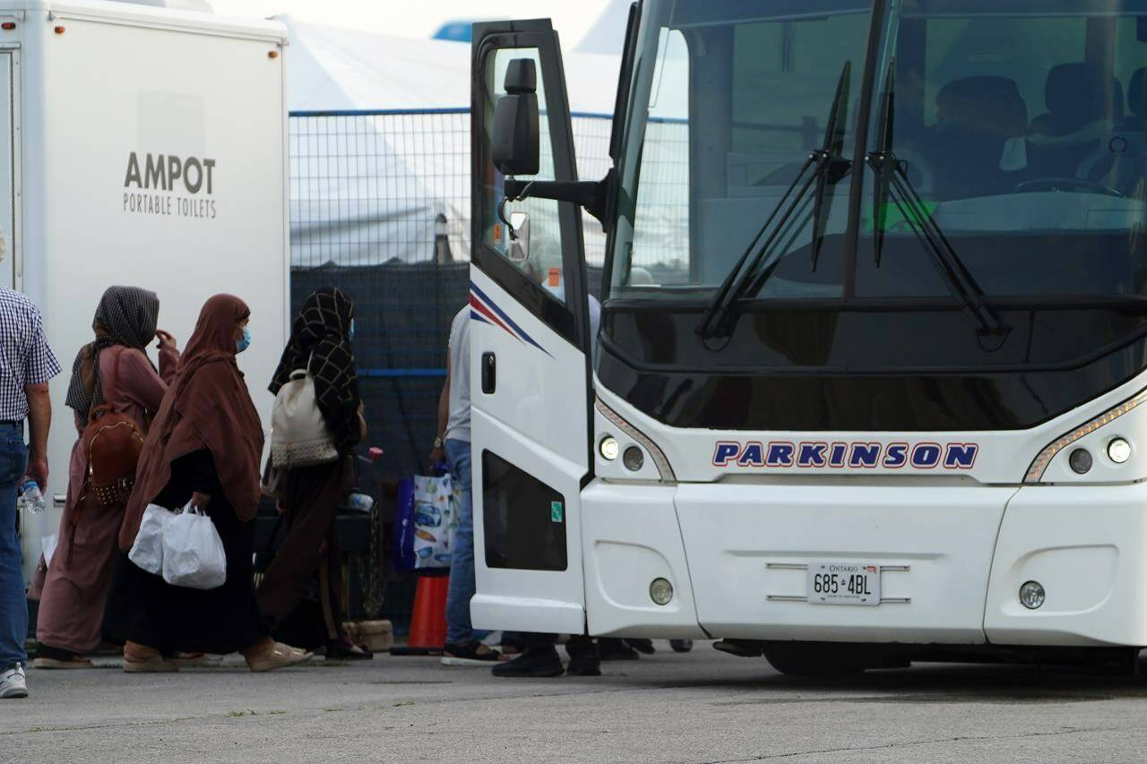 Refugees from Afghanistan and Canadian Citizens board a bus after being processed at Pearson Airport in Toronto, Tuesday, Aug 17, 2021, after arriving indirectly from Afghanistan. THE CANADIAN PRESS/Sean Kilpatrick